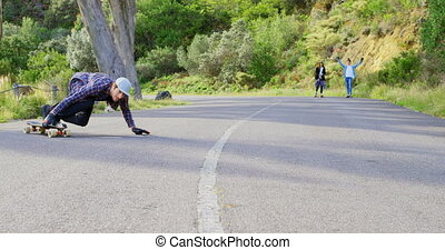 Front view of cool young caucasian man doing skateboard trick on downhill at countryside road 4k