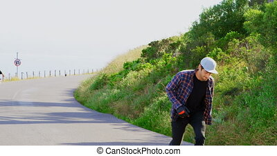 Front view of cool young caucasian skateboarders skating on downhill at countryside 4k