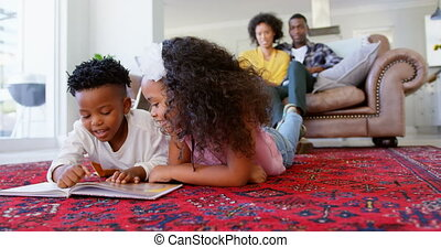 Front view of cute black kids reading story book in living room at comfortable home 4k