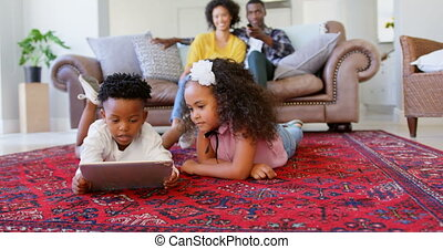 Front view of cute black kids using digital tablet in living room at comfortable home 4k