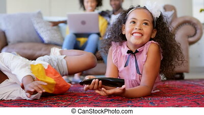 Front view of cute black siblings watching television in living room at comfortable home 4k