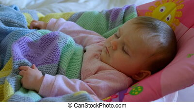 Front view of cute caucasian baby relaxing on baby bed in a comfortable home 4k