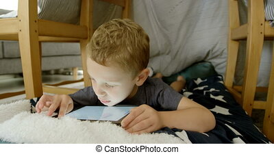 Front view of cute caucasian boy using digital tablet in a comfortable home 4k