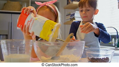 Front view of cute Caucasian siblings baking cookies in kitchen of comfortable home 4k