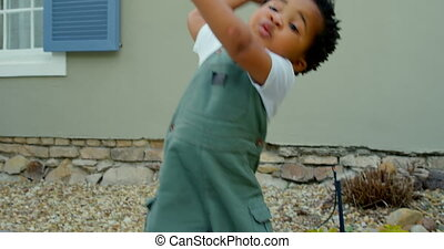 Front view of cute little black baby playing in back yard of their home. He is throwing pebbles 4k
