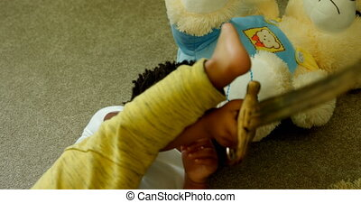 Front view of cute little black boy playing and lying on floor of comfortable home 4k