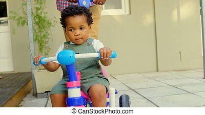 Front view of cute little black boy riding on tricycle in back yard of their home 4k