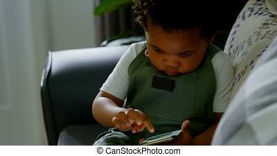 Front view of cute little black boy sitting on couch and using mobile phone in a comfortable home 4k