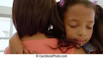 Front view of cute little black girl embracing her mother in living room of comfortable home 4k