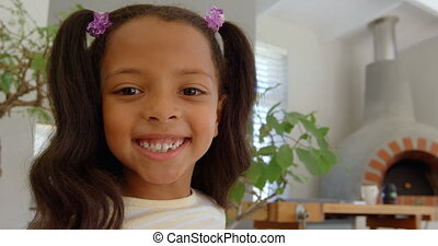 Front view of cute little black girl looking at camera in a comfortable home 4k