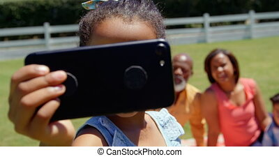 Front view of cute little black girl with family clicking selfie on mobile phone in the park 4k