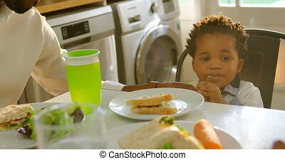 Front view of cute little black son eating food at dinning table in kitchen of comfortable home 4k