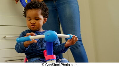 Front view of cute little black son playing and sitting on tricycle in a comfortable home 4k