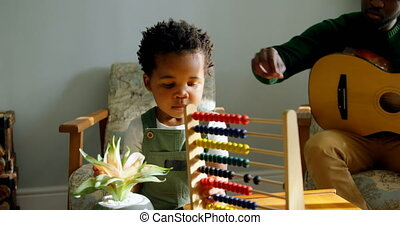 Front view of cute little black son playing with abacus in living room of comfortable home 4k