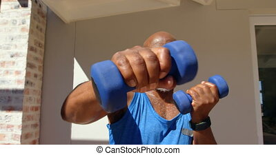 Front view of determined mature black man exercising and looking at camera in backyard of home 4k