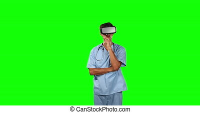 Front view of doctor using virtual reality with green screen