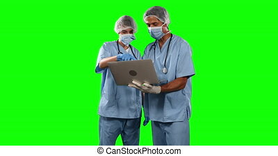 Front view of doctors watching some results on laptop with green screen