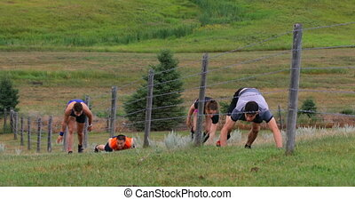 Front view of fit Mixed-race people crawling through barbed ...