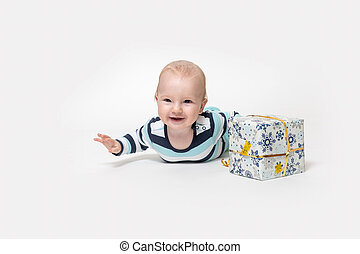 """Front view of """"flying"""" toddler boy is posing with the Christmas package."""