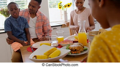 Front view of happy black family eating food on dining table in a comfortable home 4k