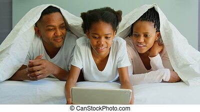 Front view of happy black family using digital tablet on bed in a comfortable home 4k