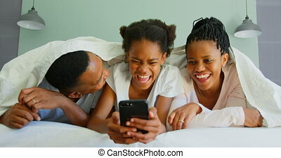 Front view of happy black family using mobile phone on bed in a comfortable home 4k