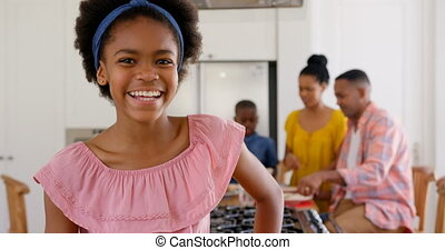 Front view of happy black girl looking at camera in a comfortable home 4k