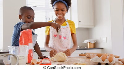 Front view of happy black siblings baking cookies in kitchen...