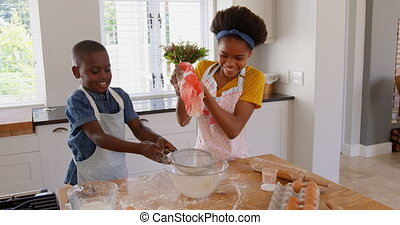 Front view of happy black siblings sifting flour in kitchen of comfortable home 4k