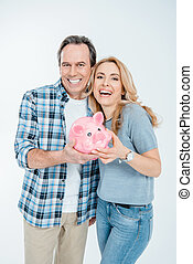 Front view of happy couple holding piggy bank on white