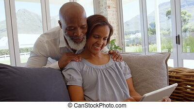 Front view of happy mature black couple using digital tablet in a comfortable home 4k