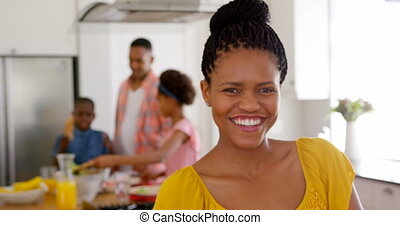 Front view of happy mid adult black woman looking at camera in a comfortable home 4k