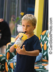 Front view of happy thirsty blond kid boy drinking lemonade, fruit tea, kombucha ice tea with peach and lemon, wellness orange drinks from plastic cup with straw, standing. Stories vertical format