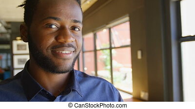 Front view of happy young black businessman looking at camera in a modern office 4k