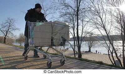 Front view of homeless mature man pushing cart - Front view...
