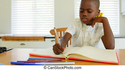Front view of little black boy doing homework at dining table in a comfortable home 4k