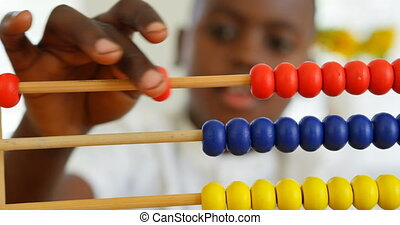 Front view of little black boy studying with abacus in a comfortable home 4k