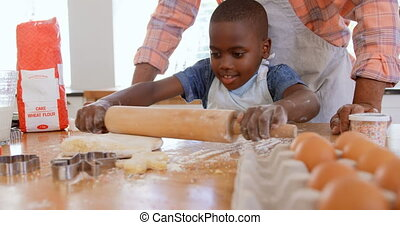 Front view of little black son rolling dough with rolling pin in kitchen of comfortable home 4k