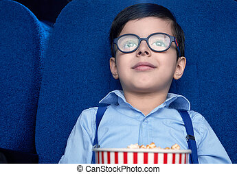 Front view of little boy watching excited film in cinema