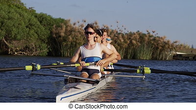 Front view of male rower team rowing on the lake - Front ...