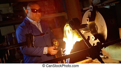 Front view of male worker creating glass in glass factory. Male worker heating glass 4k