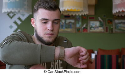Front view of man checking messages on smartwatch while he is sitting in the pub
