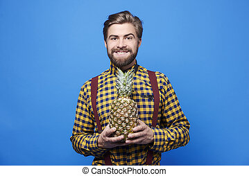 Front view of man holding a pineapple