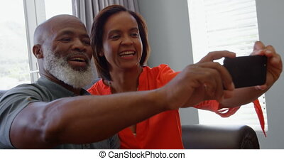 Front view of mature black couple clicking selfie with mobile phone in a comfortable home 4k