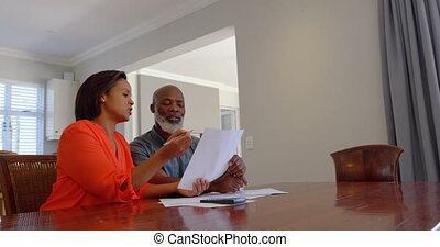 Front view of mature black couple discussing domestic bills in a comfortable home 4k