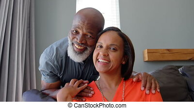 Front view of mature black couple looking at camera in a comfortable home 4k