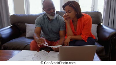 Front view of mature black couple sitting on the couch and discussing bills in a comfortable home 4k