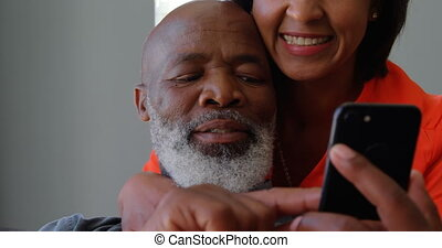 Front view of mature black couple using mobile phone in a comfortable home 4k