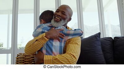 Front view of mature black father embracing his son in living room of comfortable home 4k