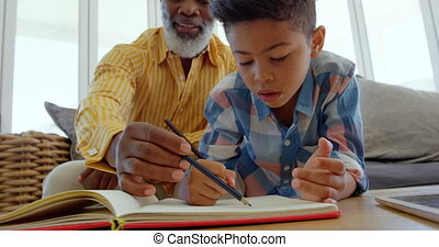 Front view of mature black father helping his son with homework in a comfortable home 4k
